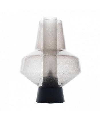 DesignSuccessful Living from Diesel with FoscariniKonceptMetal Glass 2 bordlampen er resultatet af en spændende sammensmeltning af en århundredgammel tradition for mundblæst glas samt den industrielle tilgang til metalforarbejdning.Visuelt er Metal Glass lige lukt ud af alkymistens skumle kælderlaboratorium efter en hastig parring med en Gotisk lanterne.Lampen udmærker sig ved en kompakt og næsten opaliseret uigennemsigtighed, der opnåes ved at der hældes sodapulver i glasmassen mens den stadigvæk er smaltet og rødglødende. Efterfølgede sker der en kemisk reaktion der danner et utal af bobler, der når lampen er tændt omdannes til æteriske lysende partikler.Pyrex cylinderen inde i lampen fungere som lysspreder men er samtidig en intrigant del af designet. Successful Living from Diesel lamperne er som oftest bestillingsvarer men de kan normalt være hjemme inden for 1-3 uger.