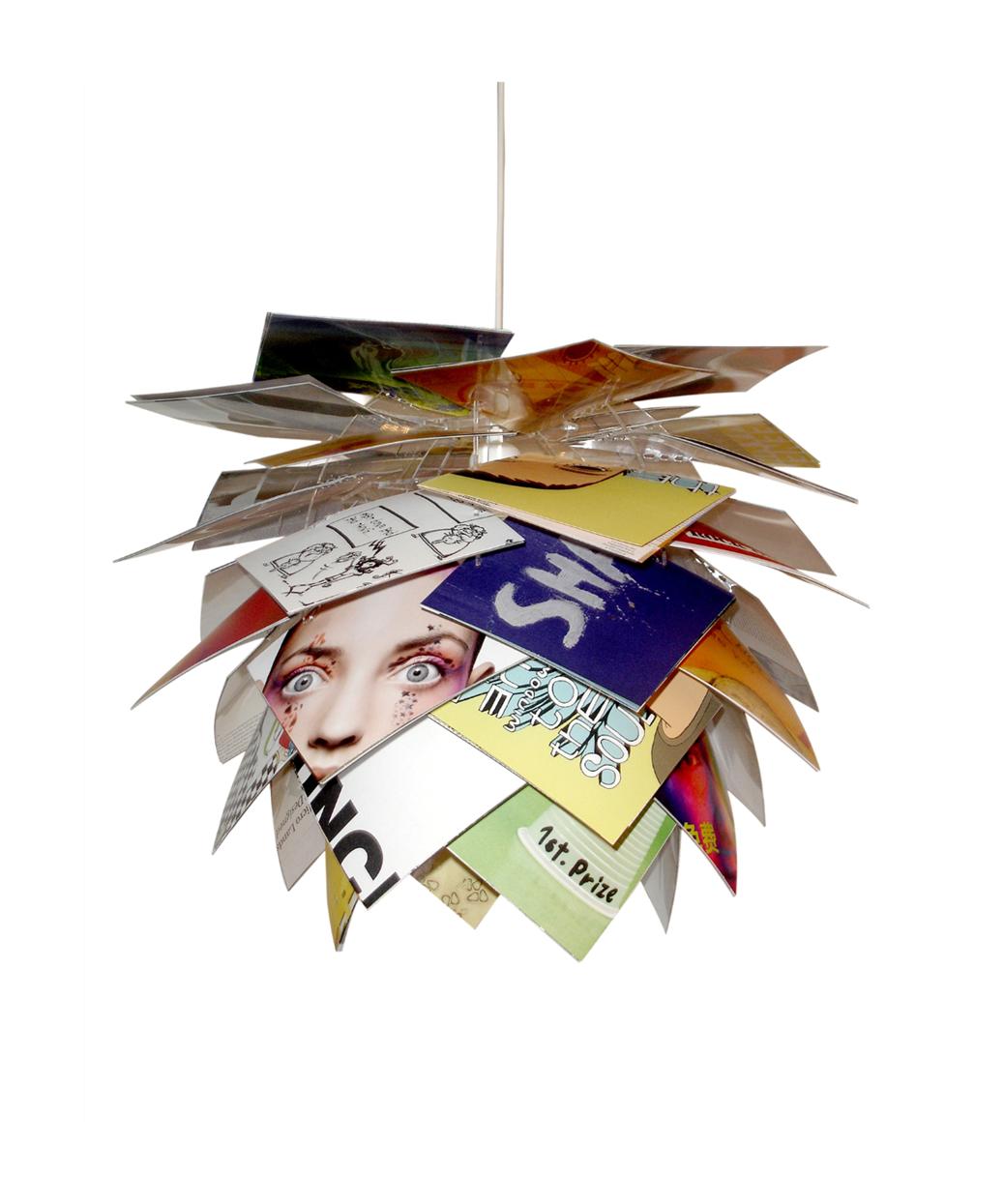 DesignFrank Kerdil for Dyberg Larsen  Koncept PineApple Pendel Magazine er en ny spændende og fleksibel Pendel, der også kan anvendes som gulvlampe eller til bordet.  Lampen er skabt i den bedste danske designtradition. Hele serien er bygget op omkring et næsten usynligt stel lavet af poleret akryl, hvorpå der, i denne udgave af lampen, er monteret kvadratiske sorte blade, eller plader om man vil.  Den spændende kogle form har både ananas og lotusblomst over sig og giver mange muligheder for at stramme op på indretningen. Magazine Pendlen kommer med 120 stk papir blade smat 40 stk. PVC blade.