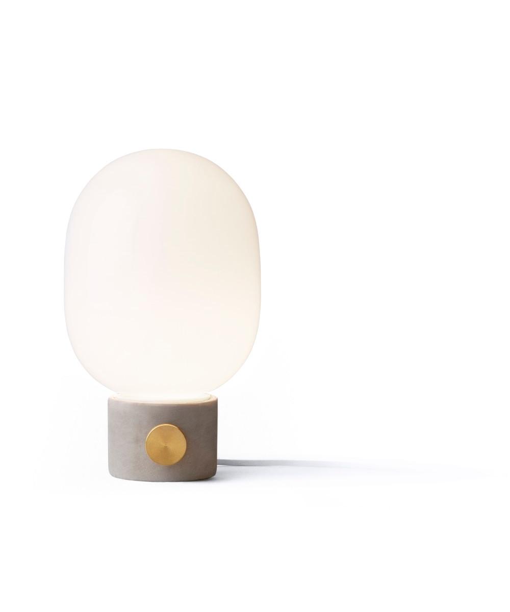DesignJonas Wagell for Menu  Jonas Wagnell har designet denne smukke og enkle JWDA bordlampe med beton, som er i familie med JWDA pendlen. Den er designet med inspiration fra olielamper og skabt i helt enkle materialer - glas og beton. Materiale valget gør lampen både delikat og rå og det enkle udtryk gør, at den kan passe ind i de fleste stilarter. Grundet diameteren på blot 17 cm kan lampen bruges rigtig mange steder. Alt fra soveværelset, skænken vindueskarmen - ja alle de steder hvor man har behovet for en smukt lampe, der giver et dejligt behageligt lys. Jonas udtaler selv: