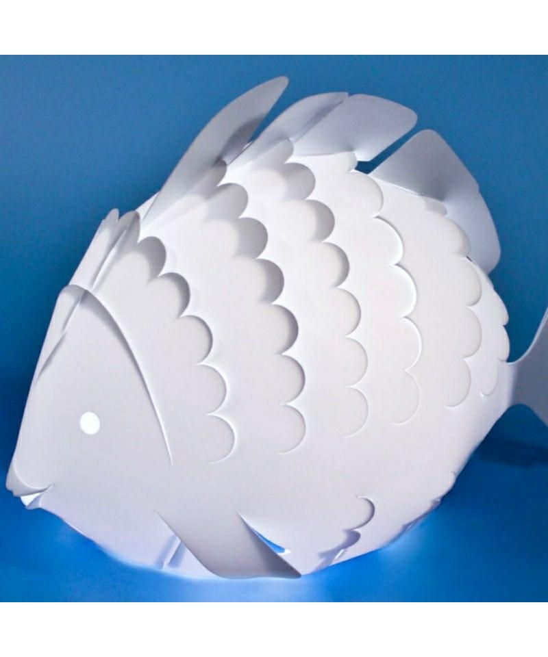DesignRamin Razina for Zoolight  Koncept Den klassiske Fisk Bordlampe fra Zoolight er en del af  serien med de søde lysende dyr. Zoolight er en serie af luksus børnelamper, som er designet meget stilrent og er efterhånden en klassiker på børneværelset. Det smarte ved denne børnelampe er, at den både har en almindelig lampefunktion samt en vågelampe funktion. Tænd/sluk kontakten der sidder på ledningen, har to indstillinger, så det er let at skifte til natlys, når godnathistorien er læst færdig. De små vågelamper har også en super smart funktion. De kan nemlig skifte farve, når man klapper i hænderne, og de er slet ikke til at stå for.  De populære Zoolight lamper er sikkerhedsgodkendt og de er derfor 100% sikker for dig og dit barn. Børnelamperne er fremstillet i kraftig, hvid polypropylen og har LED-lys, hvilket betyder at pæren er energibesparende og ikke bliver varm. Barnet har derfor ingen mulighed for at brænde sig på pæren, selvom lampen placeres ved sengen.