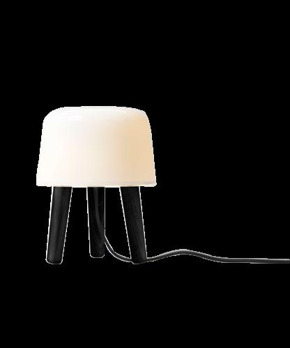 DesignNORM (Kasper Rønn & Jonas Bjerre-Poulsen) for &tradition Koncept En nuttet lille malkeskammel der er krydset med en bordlampe. Med Milk NA1 Bordlampe, har NORM, arkitekterne Kasper Rønn & Jonas Bjerre-Poulsen fundet nye spændende måder at arbejde udfra en gammel Nordiske tradition med at kombinere træ og glas. Selvom den er perfekt som en lampe, tilføjer Milk bordlampen mere end lys til dit hjem. Milk kan placeres hvor som helst og lyser op for både krop og sjæl. Milk i sort er det nyeste skud på stammen i Milk serien. Bemærk at det er mundblæst glas så der kan forekomme små luftbobler.