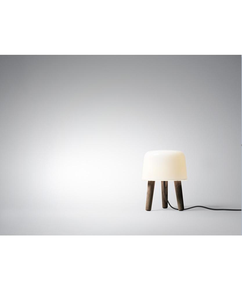 DesignNORM (Kasper Rønn & Jonas Bjerre-Poulsen) for &tradition  Koncept En nuttet lille malkeskammel der er krydset med en bordlampe. Med Milk NA1 Bordlampe, har NORM, arkitekterne Kasper Rønn & Jonas Bjerre-Poulsen fundet nye spændende måder at arbejde udfra en gammel Nordiske tradition med at kombinere træ og glas. Selvom den er perfekt som en lampe, tilføjer Milk bordlampen mere end lys til dit hjem. Milk kan placeres hvor som helst og lyser op for både krop og sjæl.  Milk i mørkolieret er det nyeste skud på stammen i Milk serien.  Bemærk at det er mundblæst glas så der kan forekomme små luftbobler.
