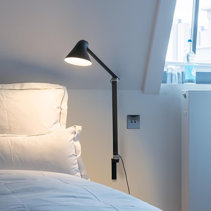 DesignNendo for Louis Poulsen  NJP Væglampe med lang arm i hvid er en smuk og enkelt væglampe designet af Oki Sato.Designet er en ny fortolkning af den klassiske arkitektlampe i et nutidigt design og med funktioner, der er tilpasset det moderne arbejdsliv, også i hjemme.  Væglampen udsender et direkte og blændfrit horisontalt lys, og samtidig reflekteres en del af lyset bagud af hovedet og oplyser således den øverste del af armen. Armaturhovedets ergonomiske design former lyset og medvirker til optimal retning på lyset. Et simpelt mekanisk system giver stor bevægelsesfrihed, så lyset altid kan indstilles optimalt i arbejdsområdet. Skærmen er hvidlakeret på indersiden, hvilket giver et komfortabelt, diffust lys.  Afbryderen sidder på hovedet og har to dæmp indstillinger og har en timerfunktion, hvor du kan vælge mellem 4 og 8 timer.  Lampen kommer med en ledning på 2,3 meter og stikprop.